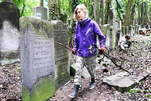 Una giovane volontaria pulisce il cimitero ebraico di Varsavia