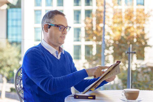 Un uomo usa OrCam MyEye per leggere
