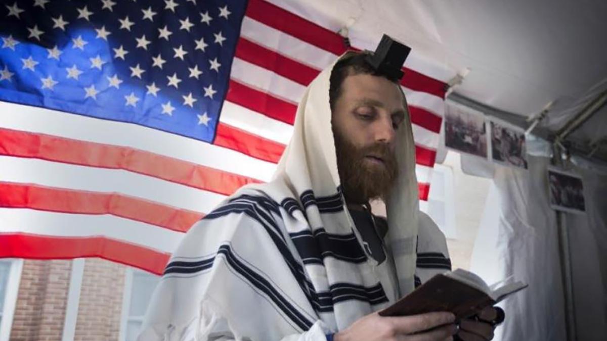 Un ebreo con sullo sfondo la bandiera americana