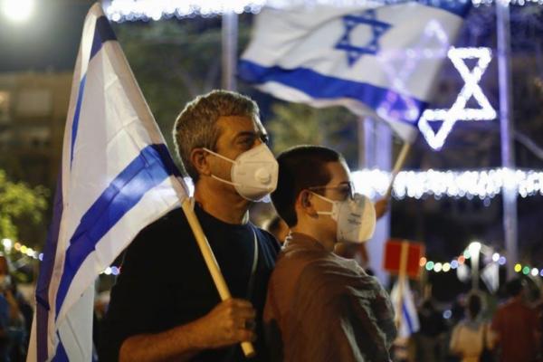 israeliani con la bandiera di Israele e le mascherine